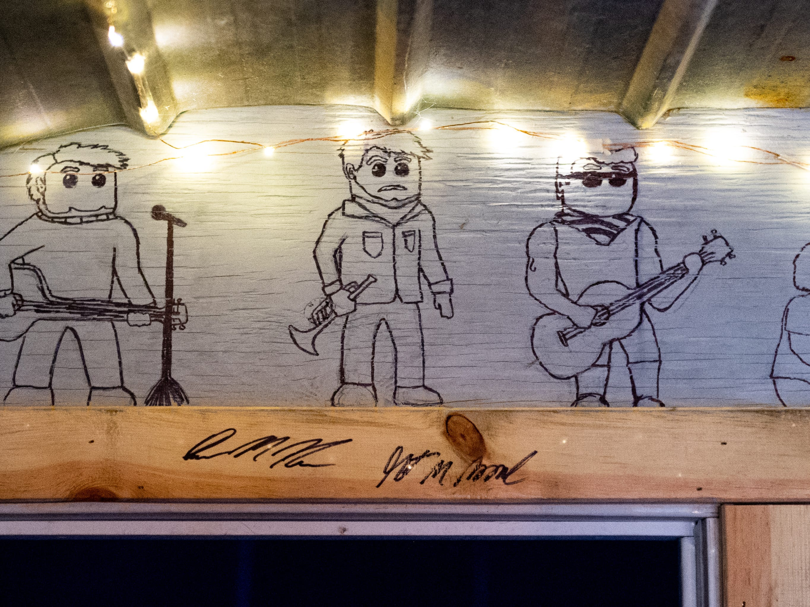 """Over the doorway to the recording studio inside of """"Crooked Coop Records,"""" are caricatures of the four founders, (left to right) Jake Puliti, Grant Moore, Connor Manley and Weston Branter. Puliti is an """"American Idol"""" hopeful whose audition is scheduled to air March 10."""