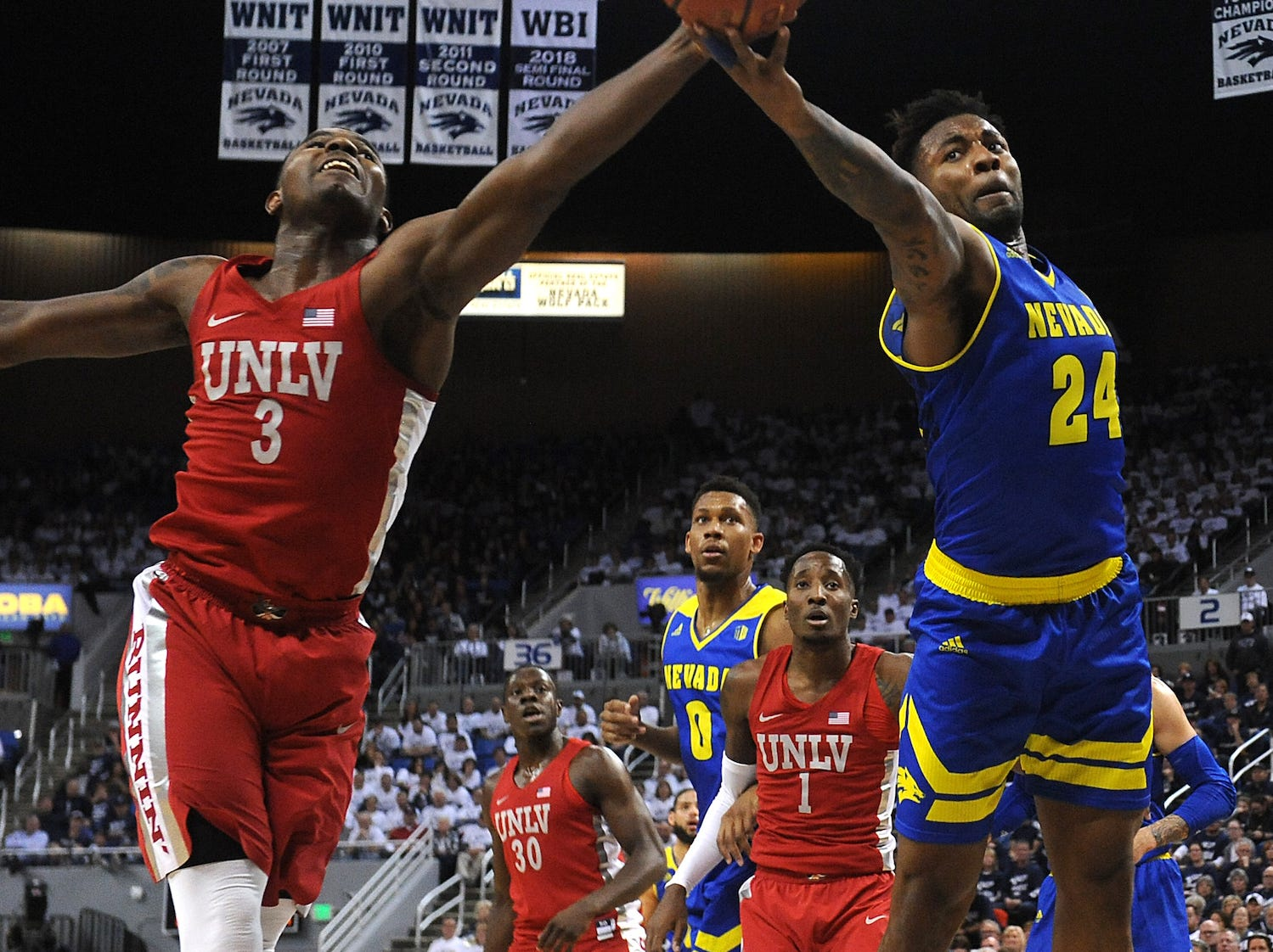 Nevada's Jordan Caroline (24) fights for a loose ball with UNLV's Amauri Hardy during the teams' game on Wednesday night.