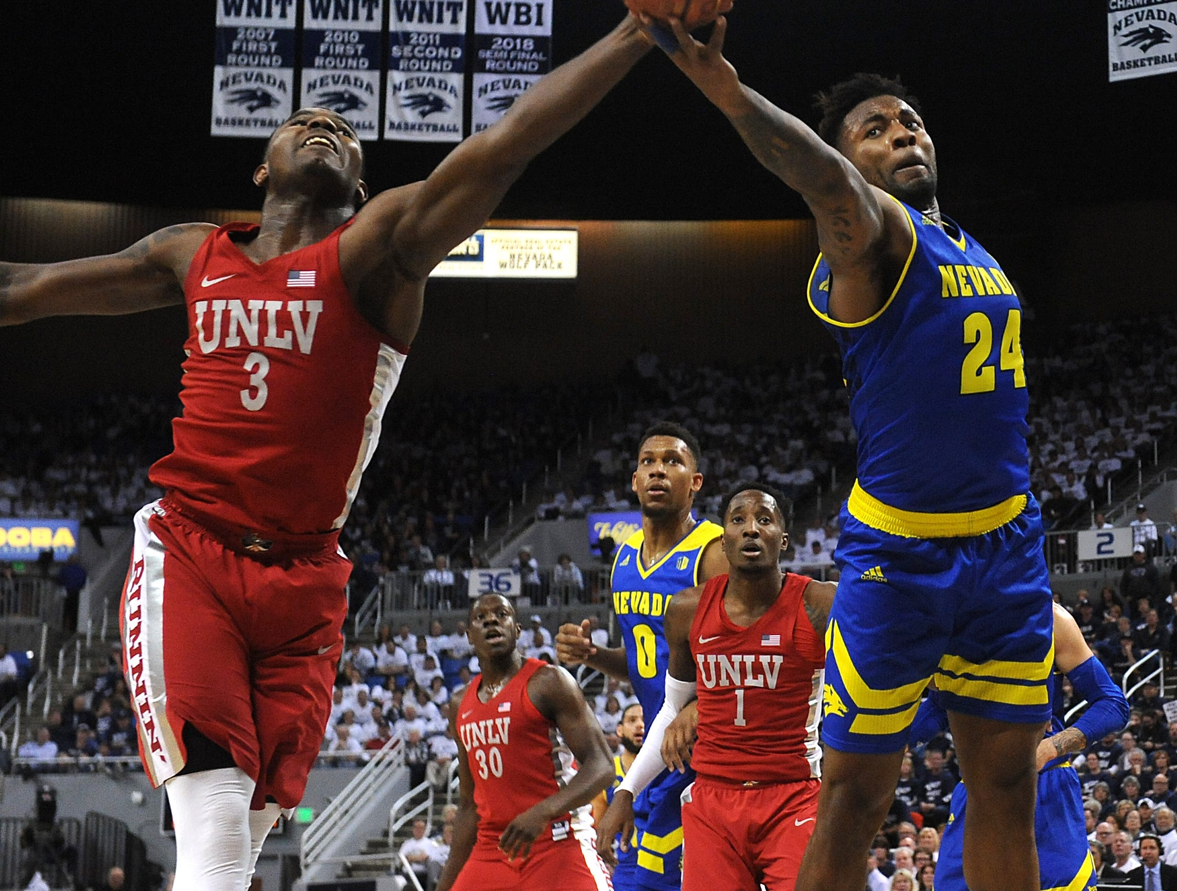 Nevada's Jordan Caroline (24) fights for a loose ball with UNLV's Amauri Hardy during their basketball game at Lawlor Events Center in Reno on Feb. 27, 2019.