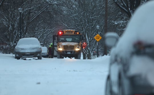 A school bus stops on a snow covered road in Rochester to pick up a student.