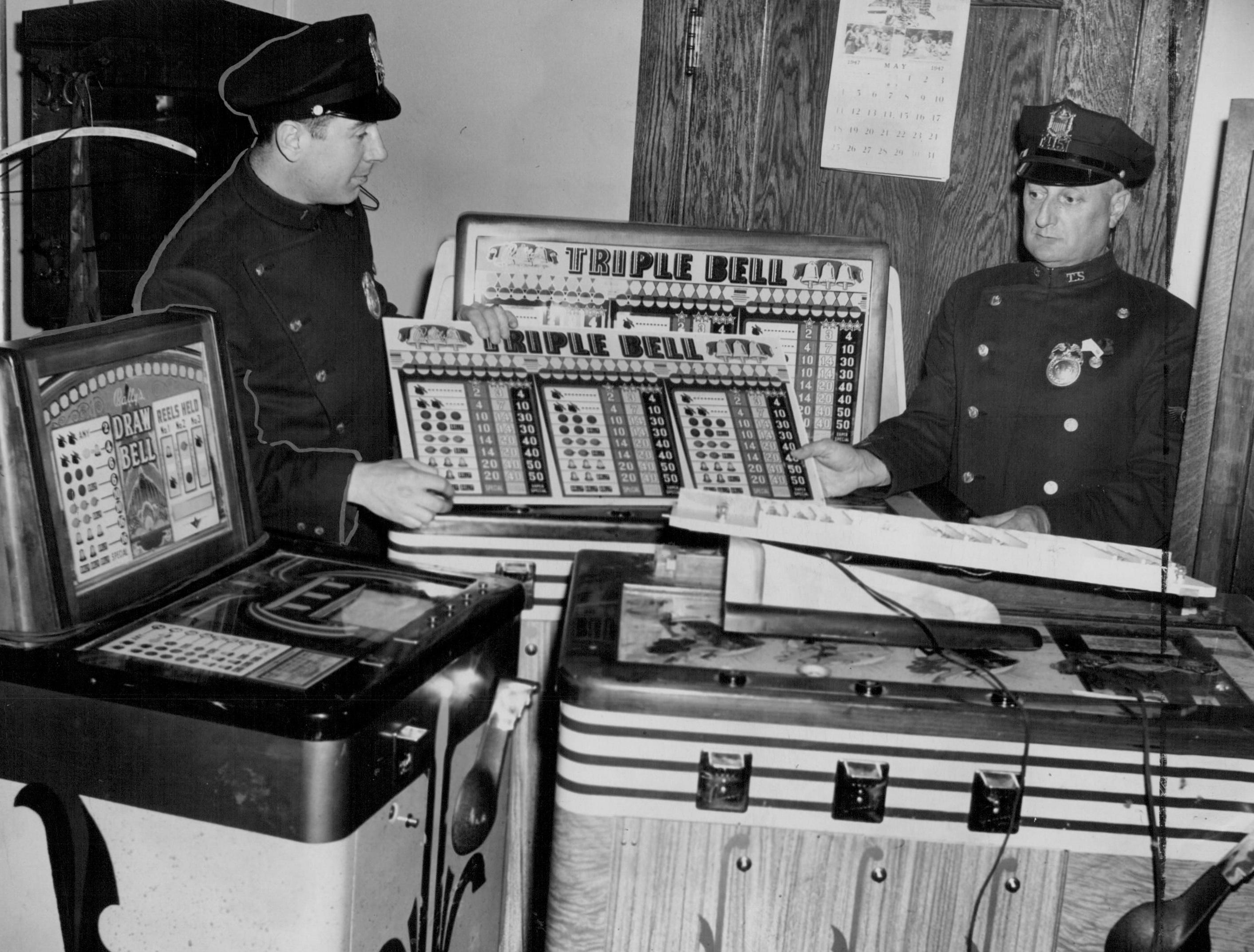 In this photo from 1947, police look over slot machines taken to headquarters after a diner on East Main Street was raided.