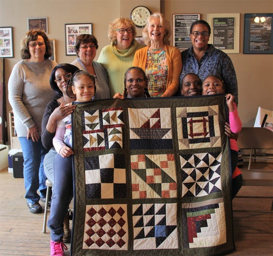 Members of a quilting group share a replica Underground Railroad sampler quilt they created during Black History Month.
