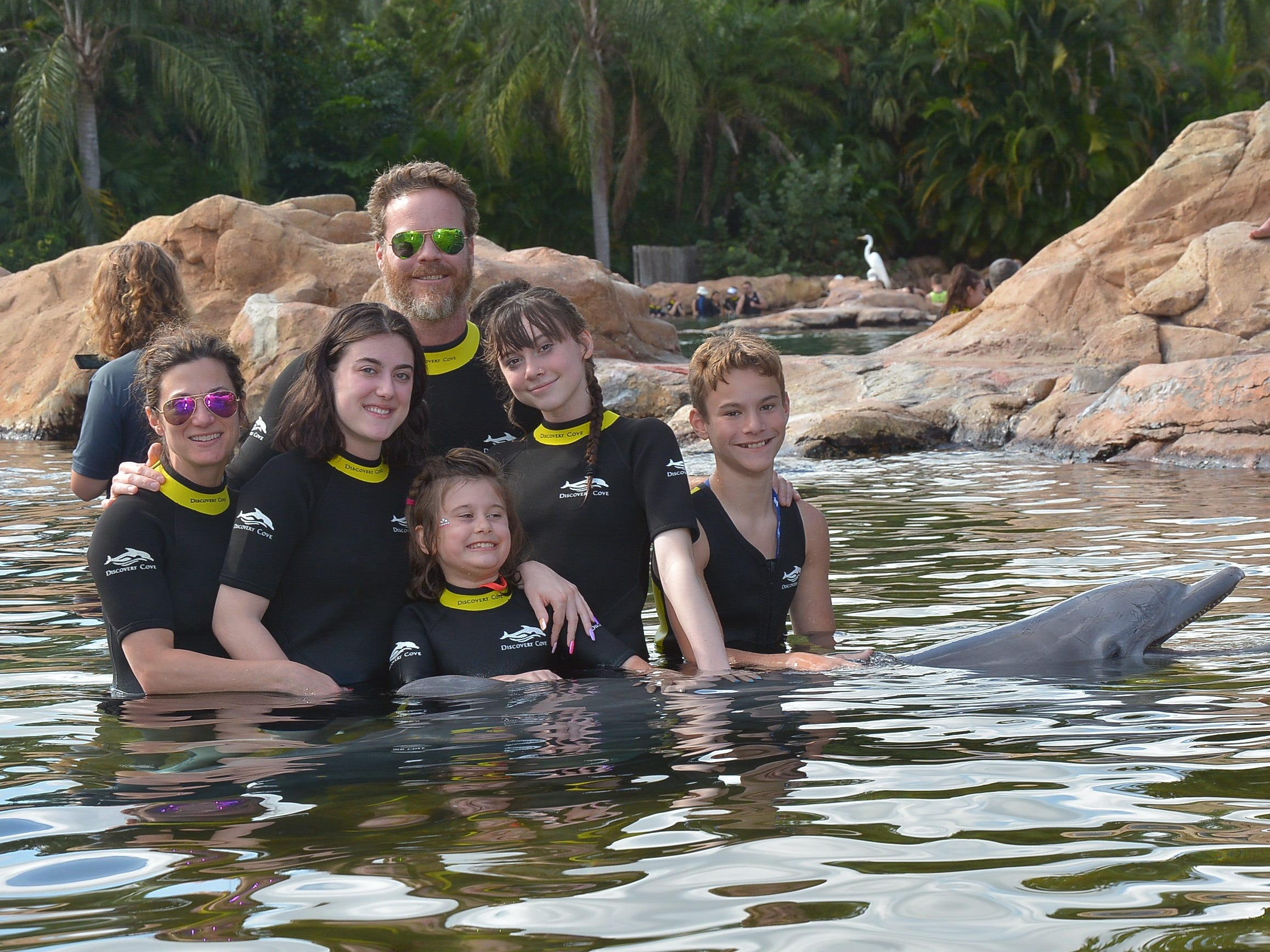 Haley Pollman, center, and her family enjoy swimming with a dolphin last December at Discovery Cove in Orlando, Florida.