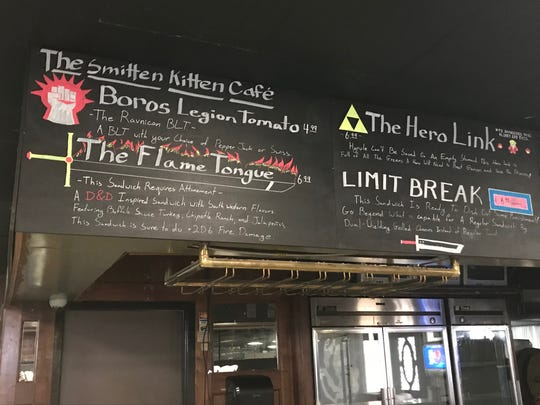 The Smitten Kitten menu references video games and tabletop games inside Phat Catz Gaming, 2017 Bryant Blvd.