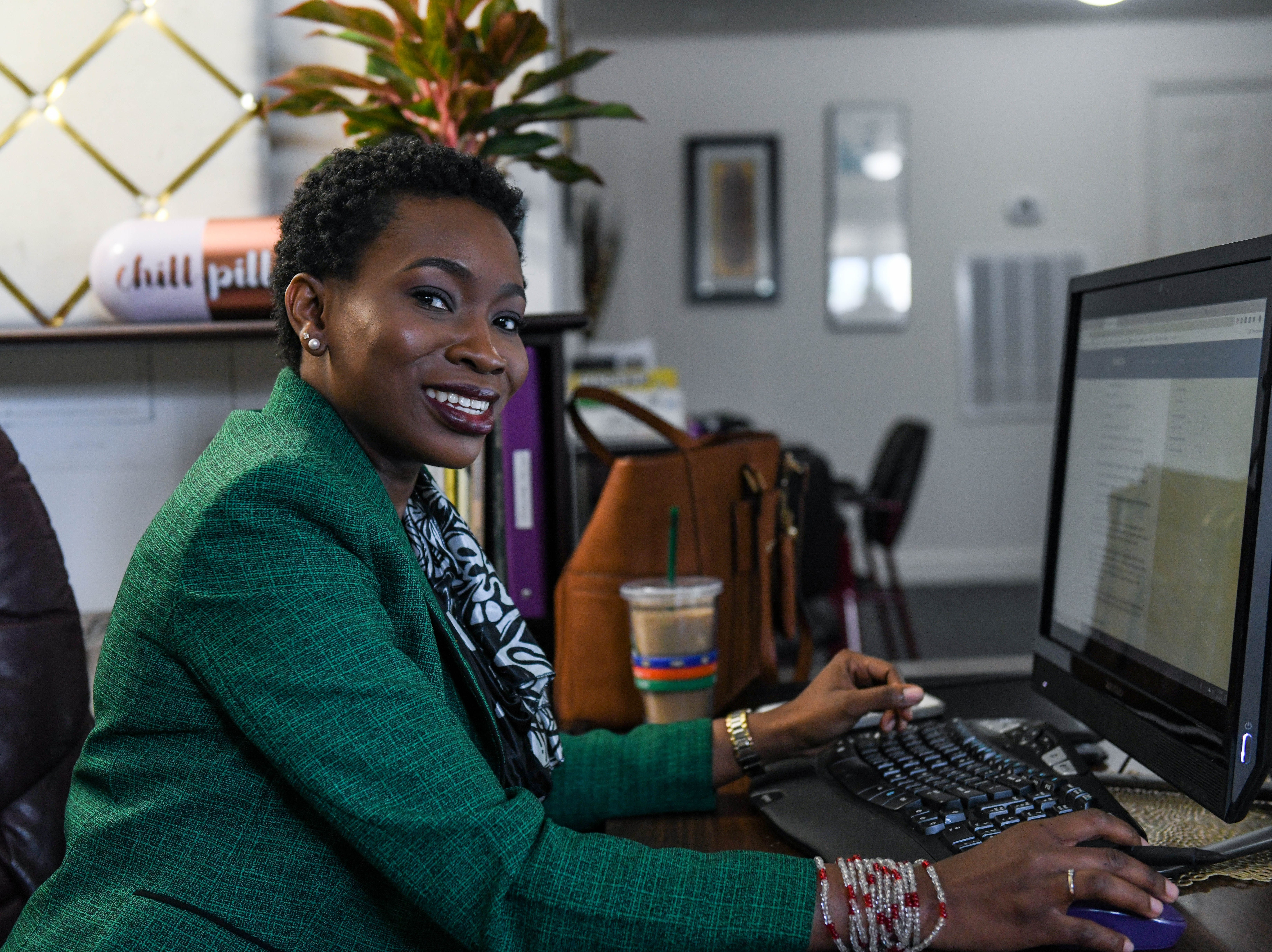 Ganiyat Badmus poses at behind the desk at her new Princess Anne business, Bluntly Coached, on Wednesday, Feb. 27, 2019.