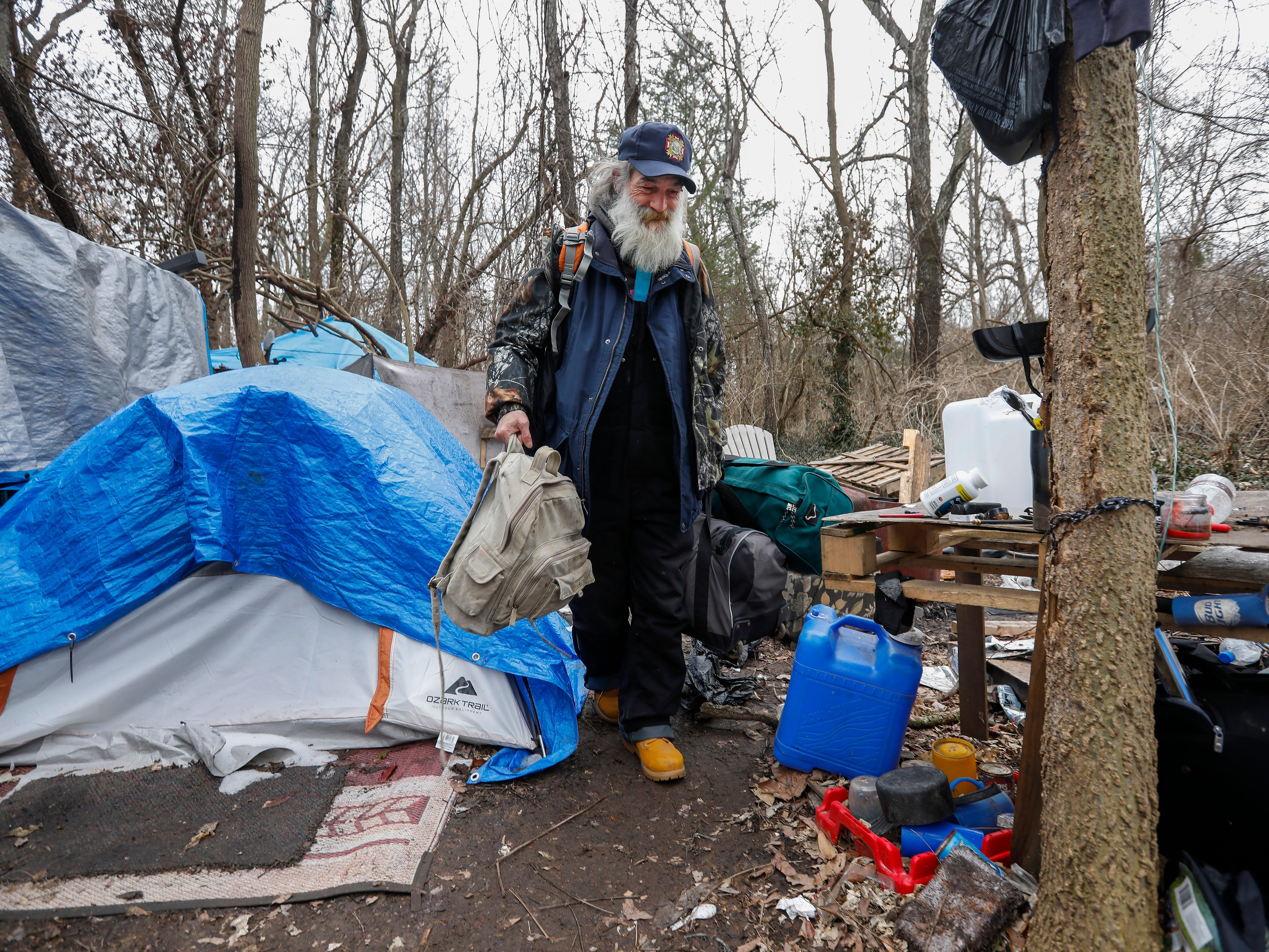 Gil Rife, who has been homeless for 3 years, carries his belongings out of the homeless camp he had been living in as he prepared to move into Eden Village on Thursday, Feb. 21, 2019.