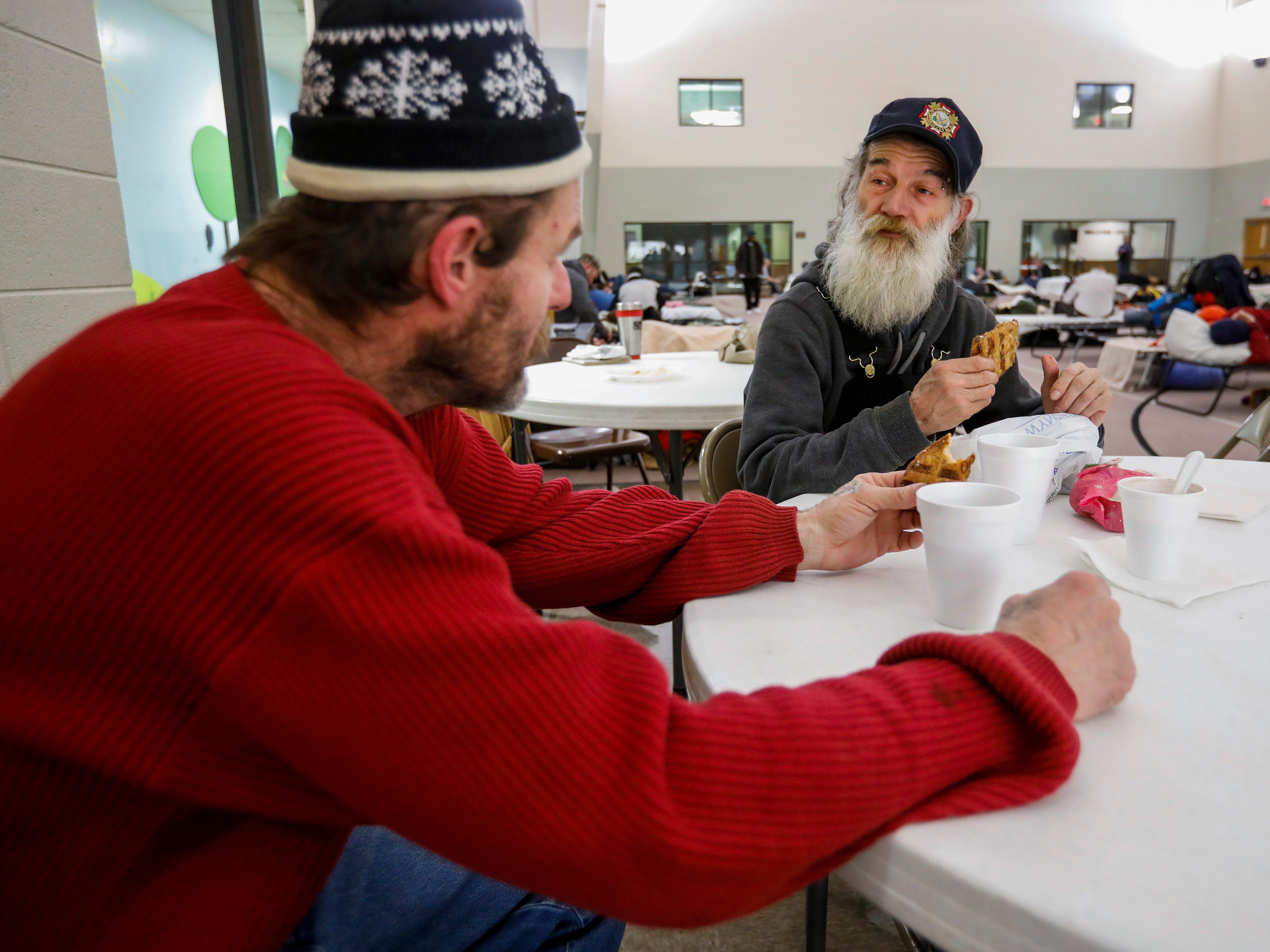 Gil Rife, right, who has been homeless for 3 years, shares some chicken with his friend Tommy (who didn't want to give his last name) at the E. Sunshine Church of Christ on Wednesday, Feb. 20, 2019. Rife was spending the night at the church which opened it's doors as a warming center after temperatures dropped below freezing.
