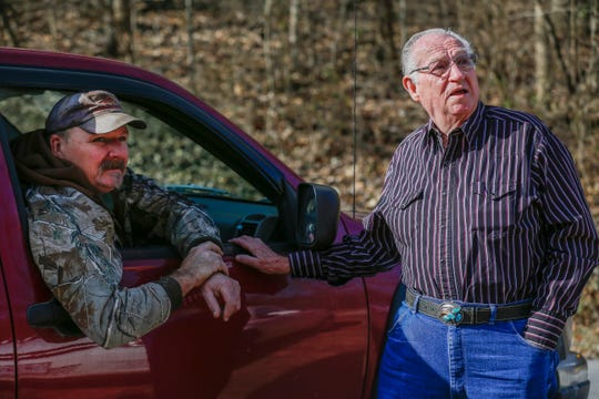 Cecil Felkner, right, and Mike Kennedy talk about a piece of an old car that sits in a tree near the intersection of Farm Roads 76 and 151. Felkner says it has been up there since he was a kid.