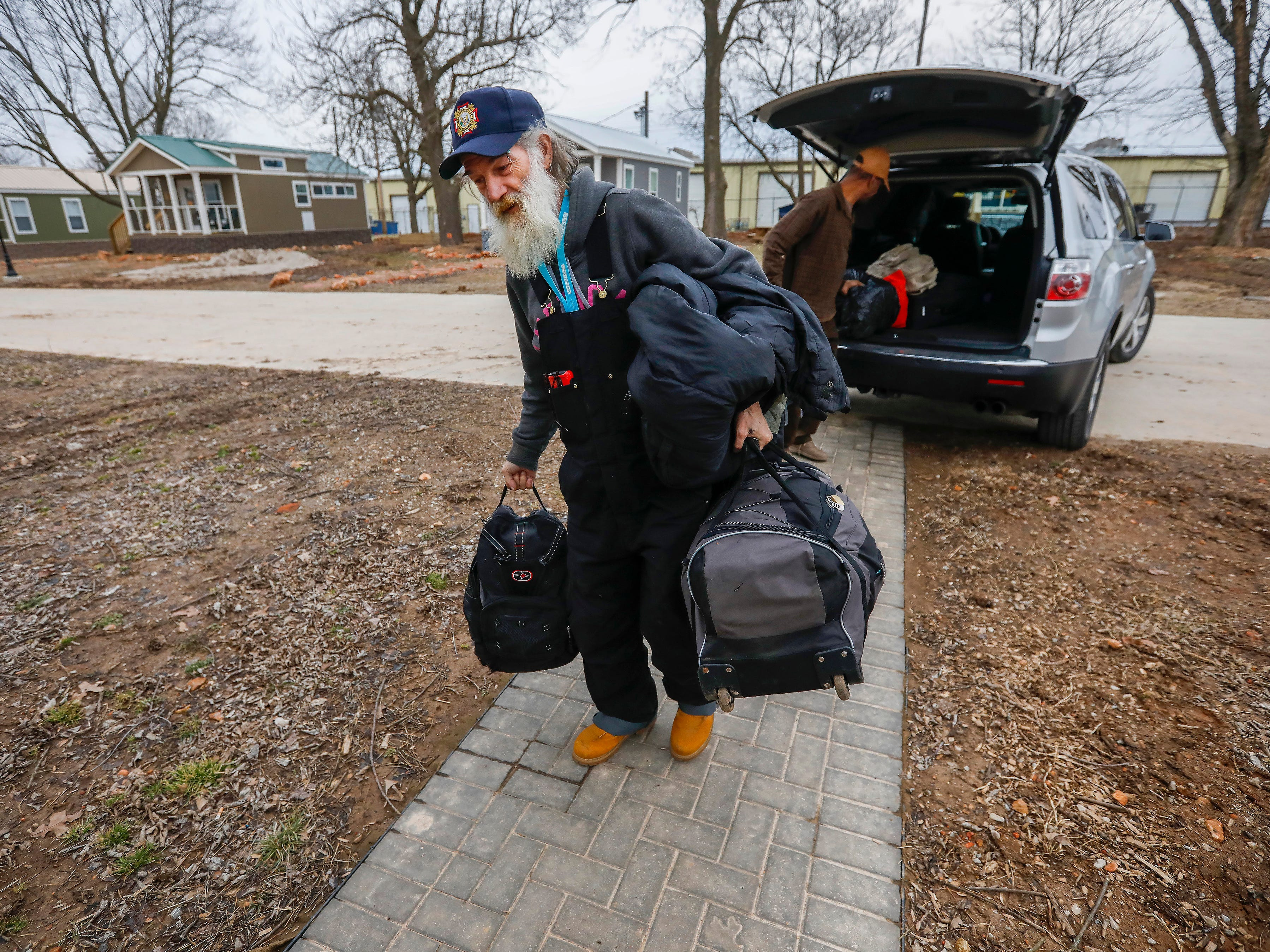 Gil Rife carries his belongings into his new home at Eden Village on Thursday, Feb. 21, 2019.
