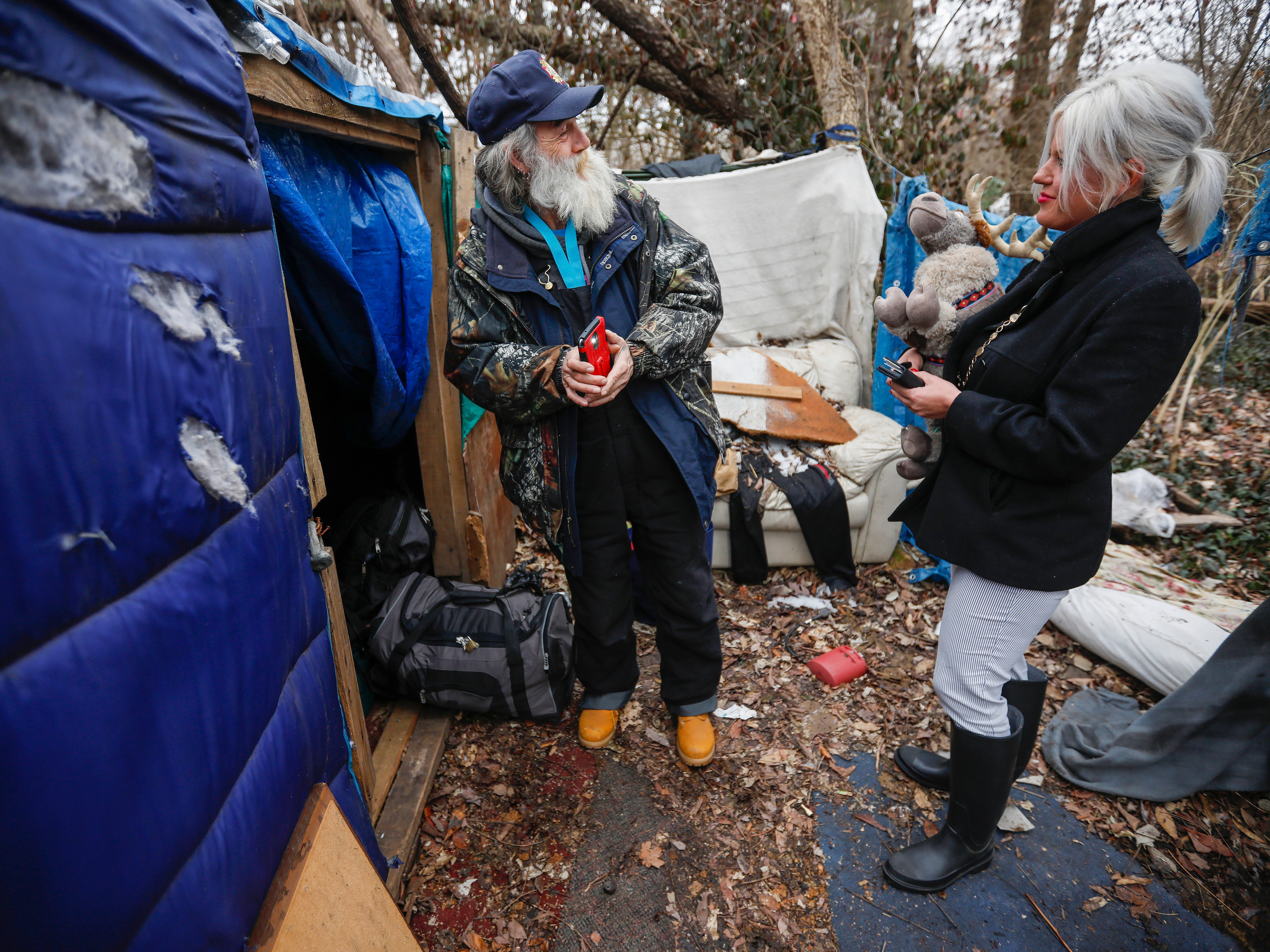 Gil Rife, left, who has been homeless for 3 years, talks with Stephanie Appleby, of NAMI, after giving her a stuffed reindeer outside the make-shift shelter he had been living in as he prepared to move into Eden Village on Thursday, Feb. 21, 2019.