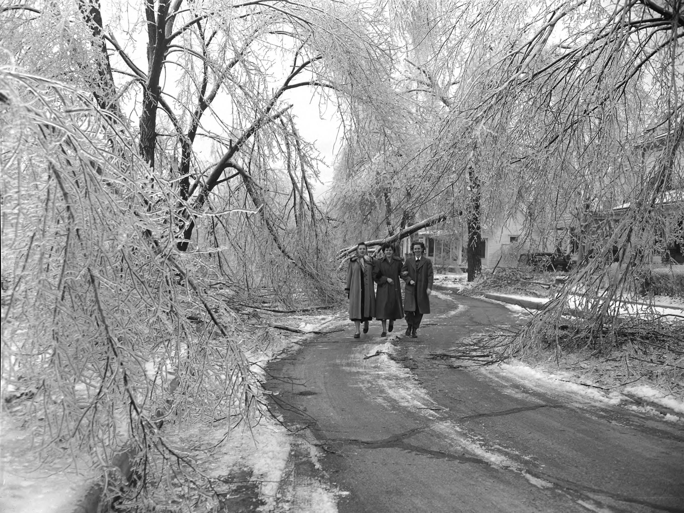 Janetta Fairchild, Betty Brooks, and Odean Burton (from left to right) on the 800 block of Connor street in Joplin, Missouri during the ice storm of January 1949. Photograph published in the Springfield Daily News on January 15, 1949.