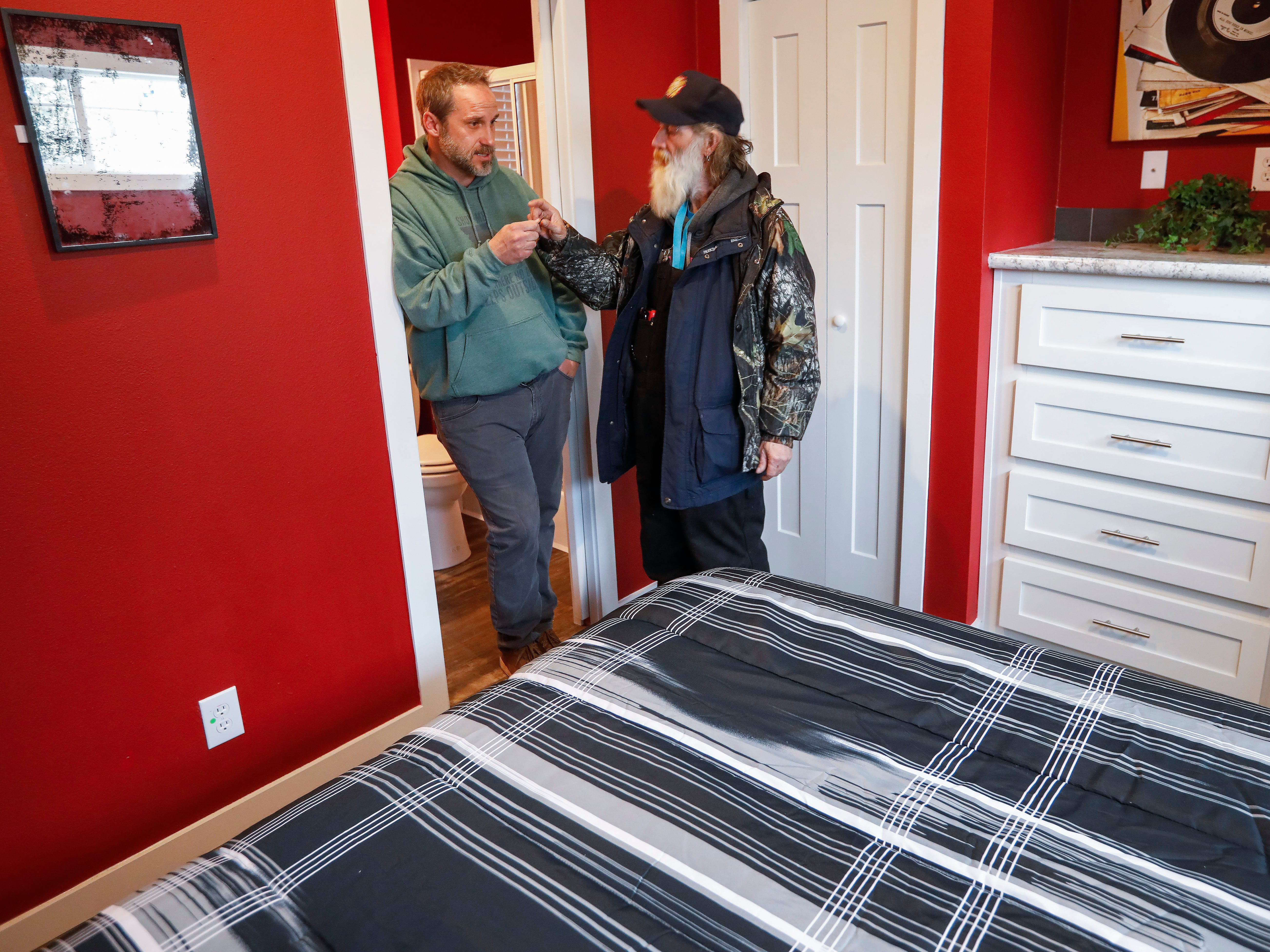 Nate Schlueter, left, COO of Eden Village, hands Gil Rife the key to his new home at the tiny home community on Thursday, Feb. 21, 2019.