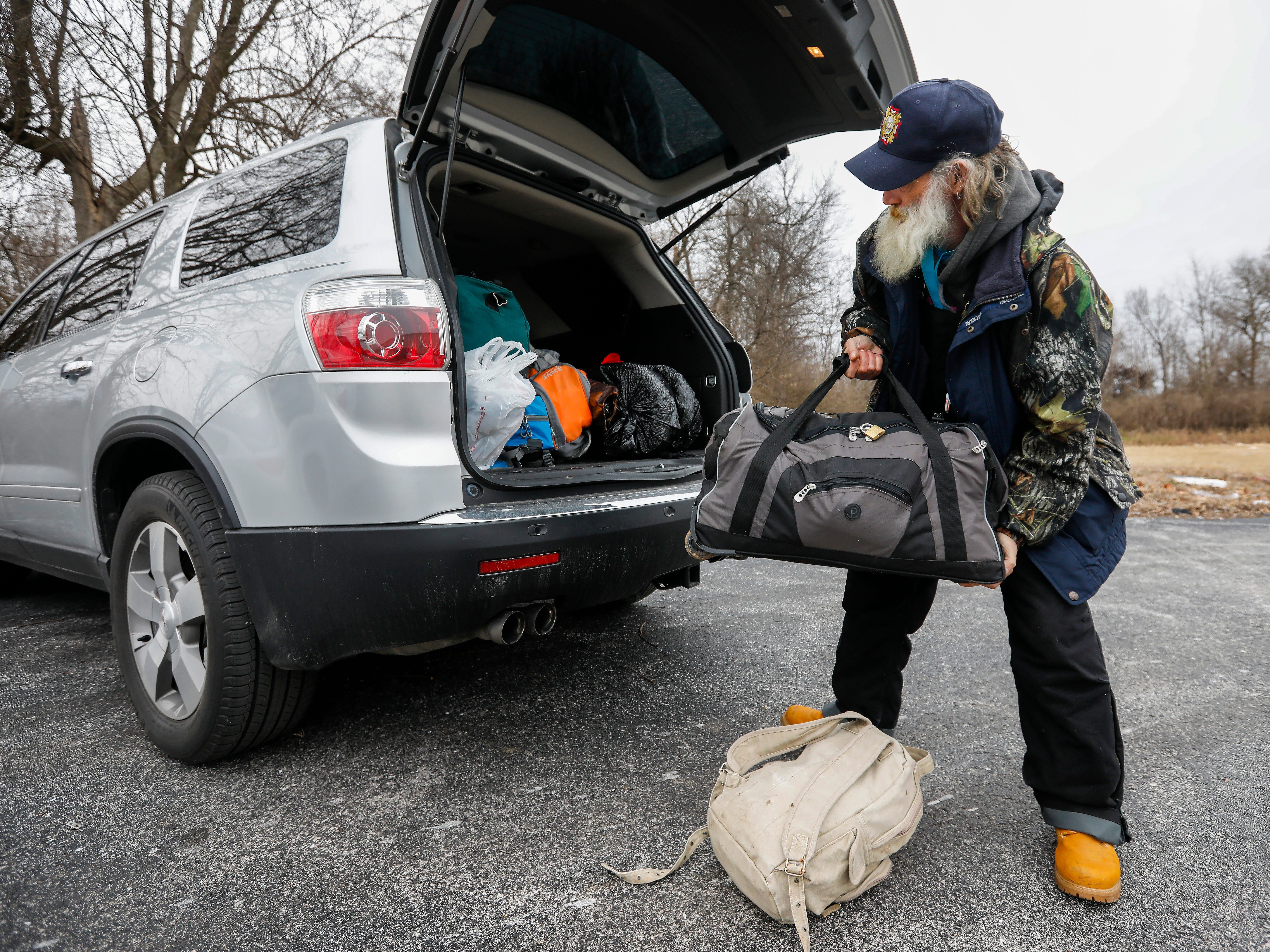 Gil Rife, who has been homeless for 3 years, loads his belongings into Stephanie Appleby's vehicle as he prepared to move into Eden Village on Thursday, Feb. 21, 2019.