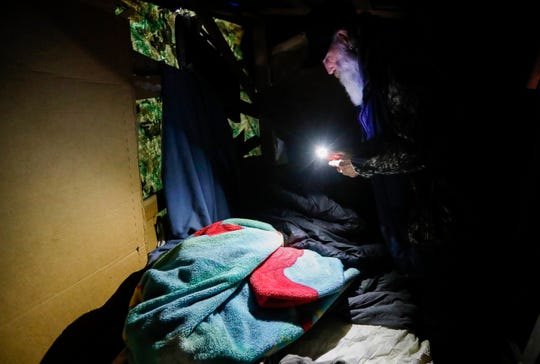 Gil Rife, who has been homeless for 3 years, uses a flashlight on his phone to gather his belongings from the make-shift shelter he had been living in as he prepared to move into Eden Village on Thursday, Feb. 21, 2019.