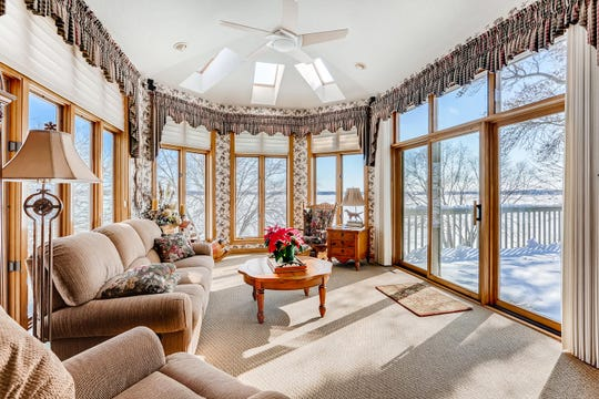 The sunroom, with its vaulted ceiling, sits at the back of the house and provides full views of the lake and access to the outdoor deck.