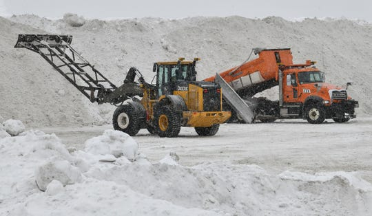 Snow is piled high after being removed from city streets and unloaded by trucks in a vacant area near the intersection of Highway 15 and Veterans Drive Tuesday, Feb. 26, in St. Cloud.