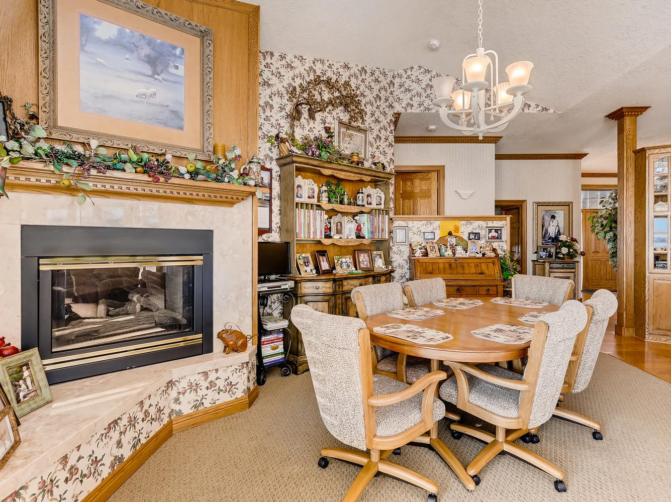 The kitchen island opens to the informal dining area warmed by a gas fireplace and large hearth.