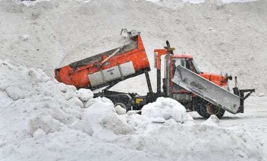 Snow is unloaded in big piles in a vacant area near the intersection of Highway 15 and Veterans Drive Tuesday, Feb. 26, in St. Cloud.