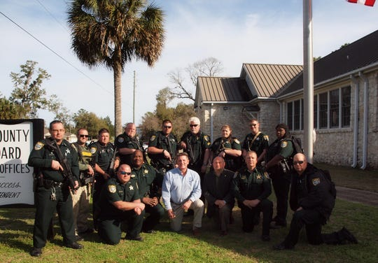 Superintendent of Wakulla County Schools Bobby Pearce, center, and Wakulla County Sheriff Jared Miller, center right, kneel, surrounded by WCSO School Resource Officers.