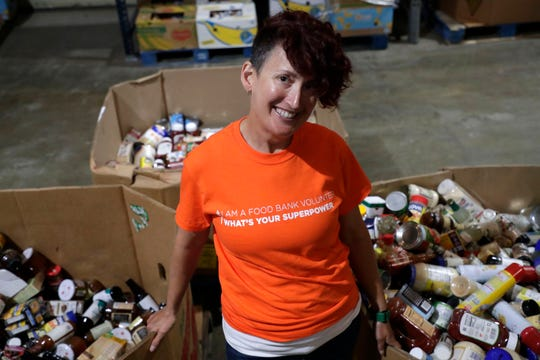 Jess Kurti, a runner, volunteer, and advocate, poses for a photo with bins full of condiments at the Tallahassee Second Harvest Food Bank, Wednesday Feb. 27, 2019.