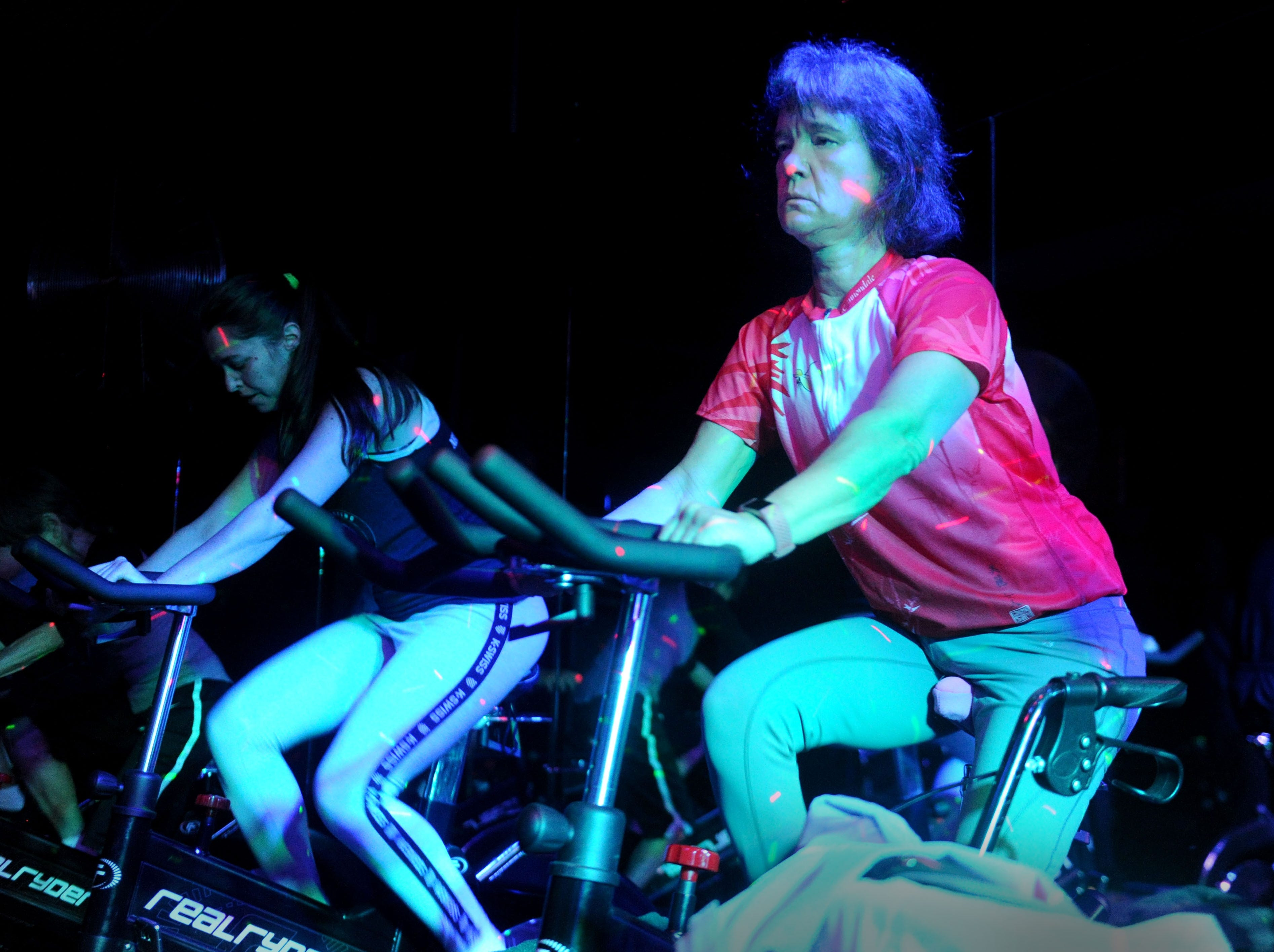 Jennifer Parkinson, left, and Debbie Jew takes a 30-minute spin class under disco lights at Agoura Fitness in Agoura Hills.