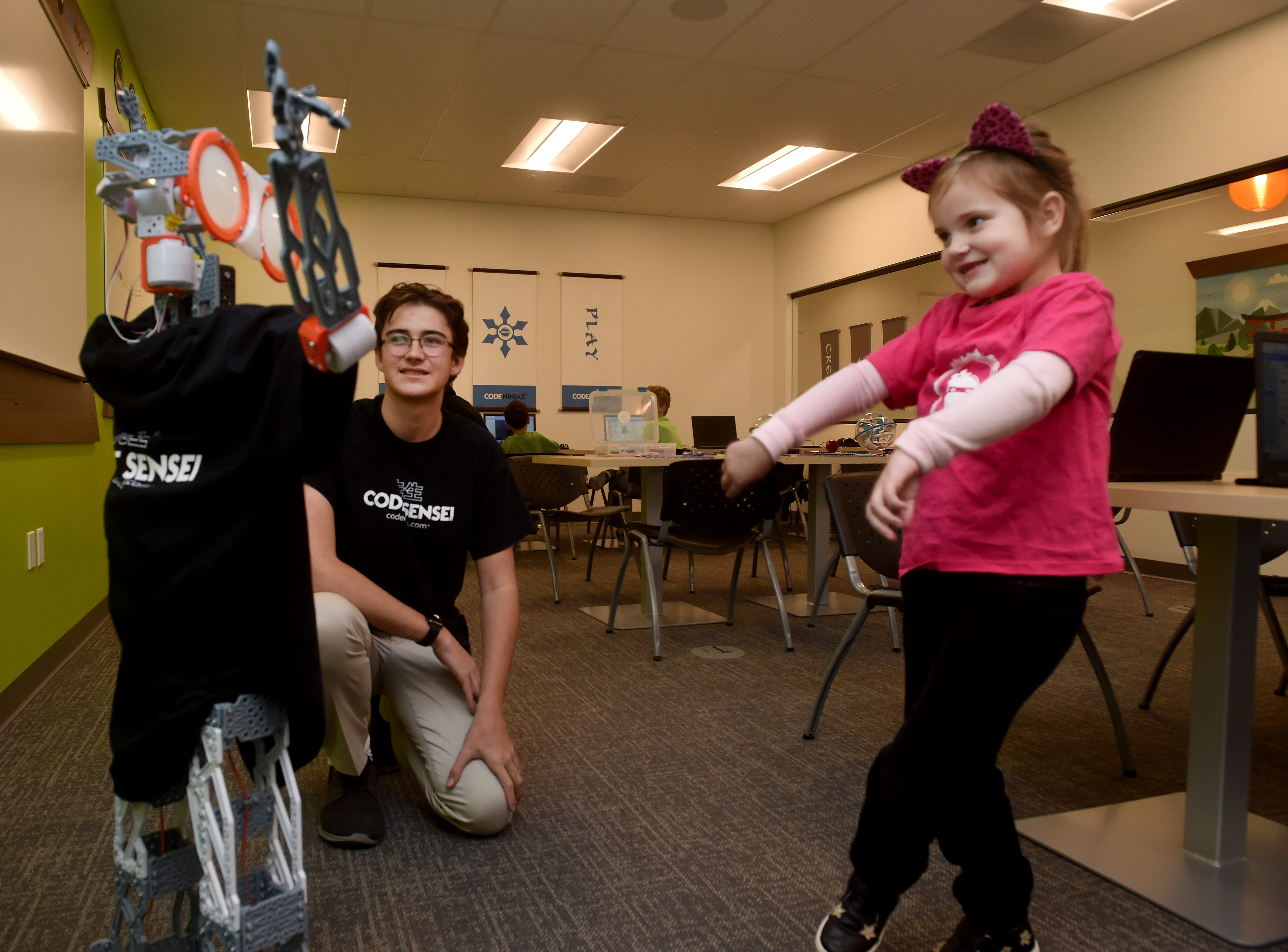 Sensei Zack Lown gives vocal commands to a robot as Coco Schulz dances with the robot at the new Code Ninjas dojo in Thousand Oaks. The facility is the first of its kind in Ventura County and the fifth franchise site in California.
