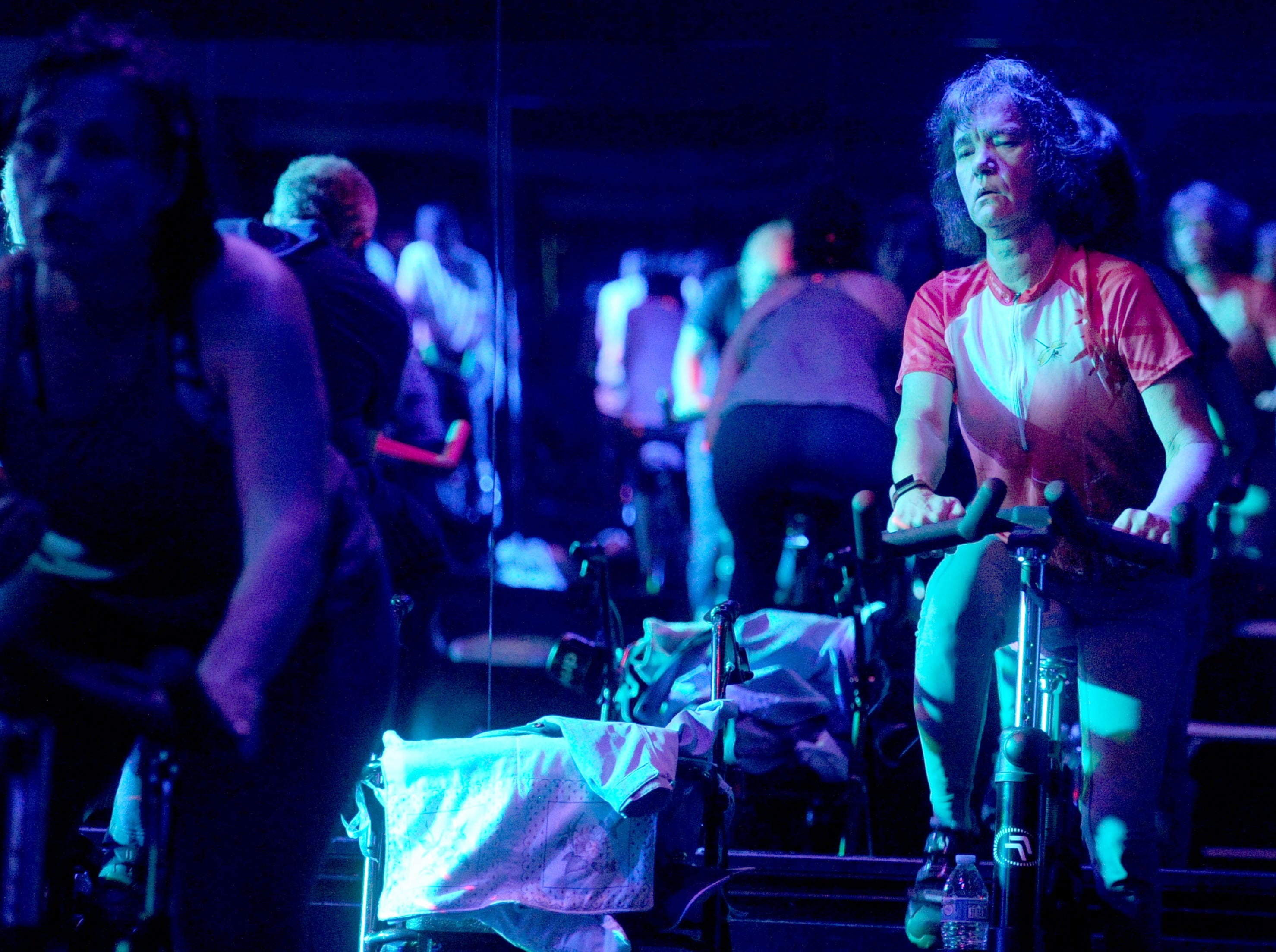 Debbie Jew, right, takes a 30-minute spin class at Agoura Fitness in Agoura Hills. The Moorpark resident was diagnosed 13 years ago with Parkinson's disease. She uses exercise to try to control the disease's progress.