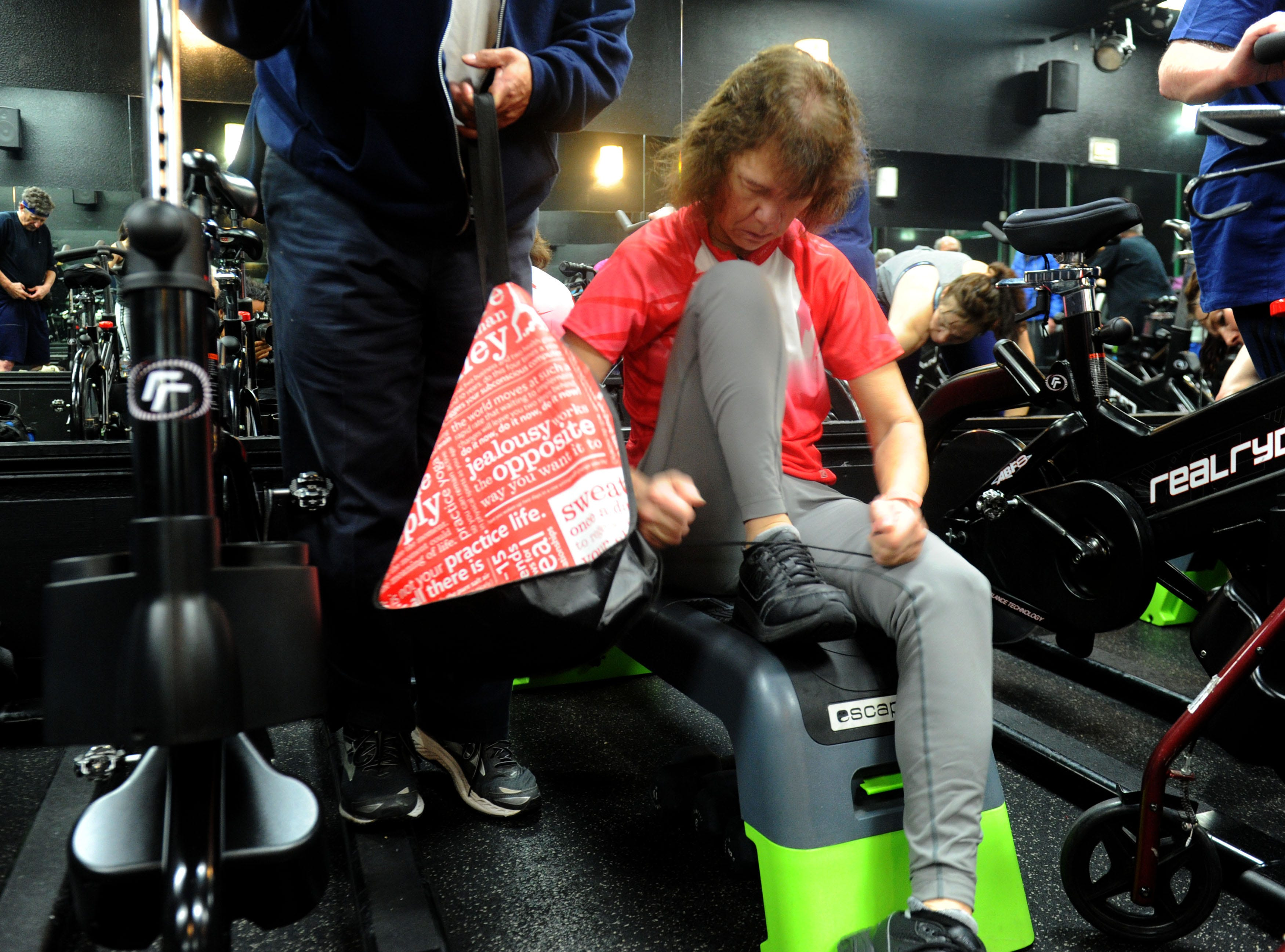 Debbie Jew puts on her tennis shoes after finishing a 30-minute spin class at Agoura Fitness in  Agoura Hills. Jew, of Moorpark, was diagnosed 13 years ago with Parkinson's disease when she was 45. She uses exercise to try to control the disease's progress.