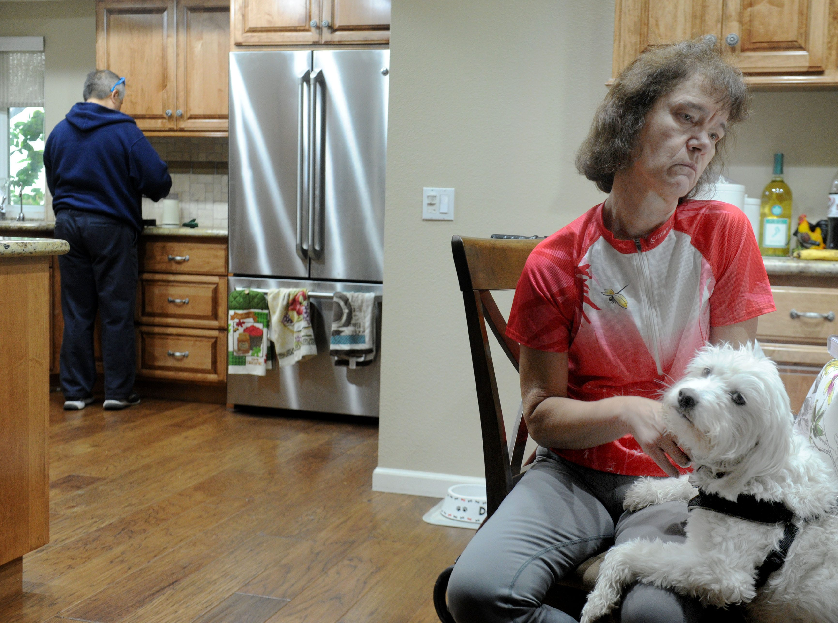 Debbie Jew pets her dog, Karly, as her husband, Frank Jew, makes a cup of coffee. She was diagnosed with Parkinson's disease about 13 years ago.