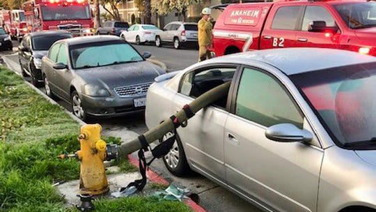 """This Tuesday photo provided by the Anaheim Fire Department and Anaheim Police Department shows a car with a fire hose running through the rear side windows. In a Twitter thread posted Wednesday, the Anaheim Fire Department asked the public: """"Ever wonder what happens when a car is parked in front of a fire hydrant and a fire breaks out."""""""
