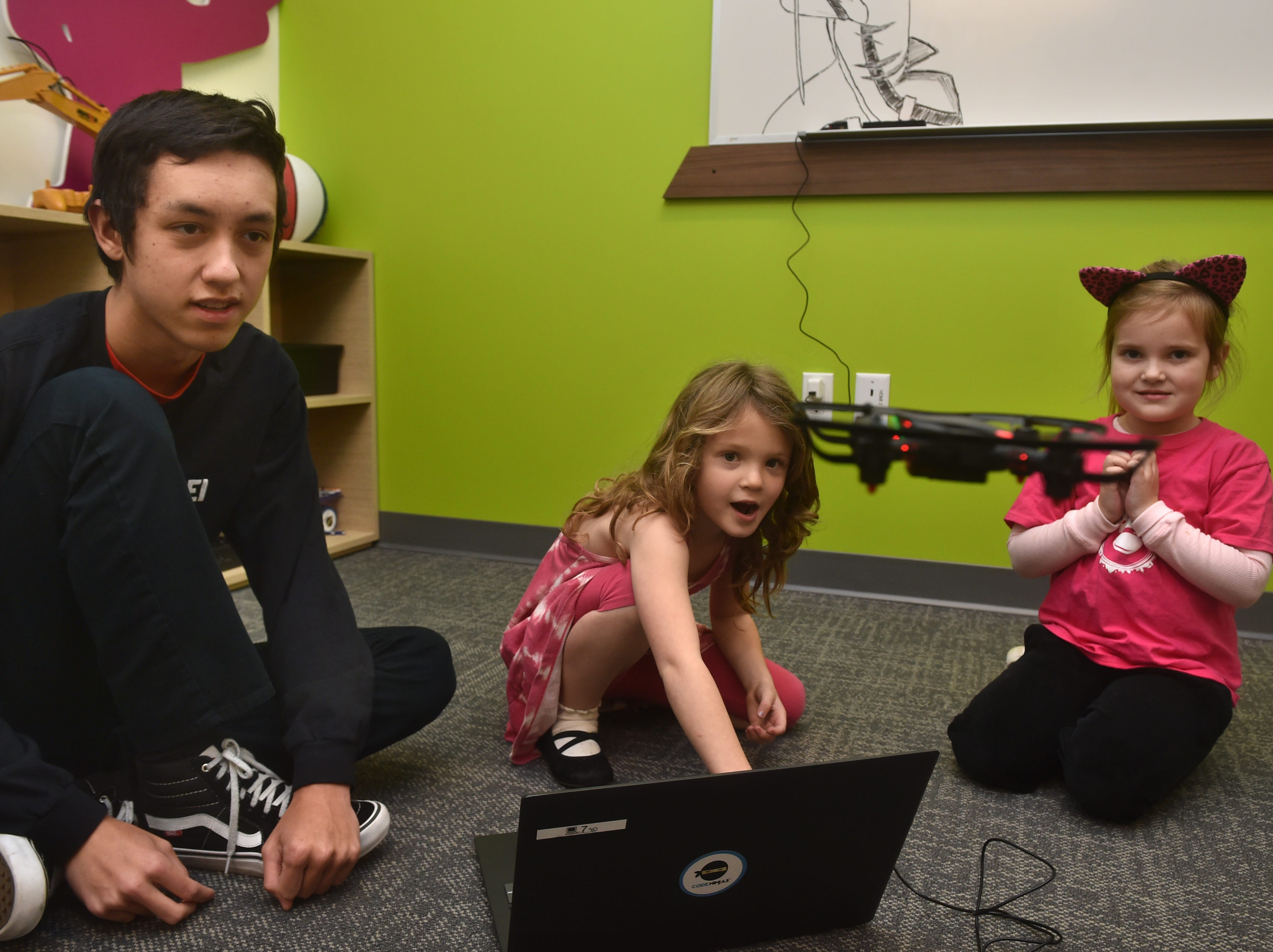 Devin Lucarelli, center, and Coco Schulz learn to fly a miniature drone with the help of sensei John McFarland at the new Code Ninjas dojo in Thousand Oaks. The facility is the first of its kind in Ventura County and the fifth franchise site in California.