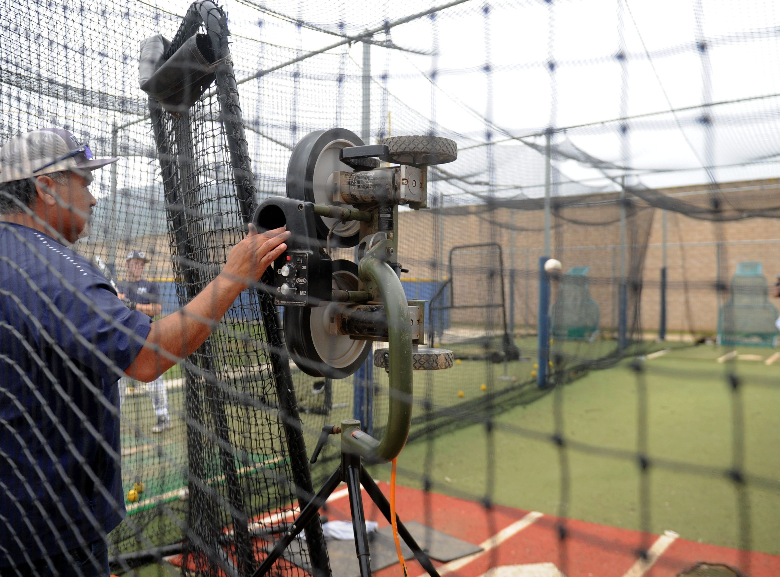 Assistant coach Phil Ramirez runs the pitching machine in the batting cage at Camarillo High's practice on Wednesday.