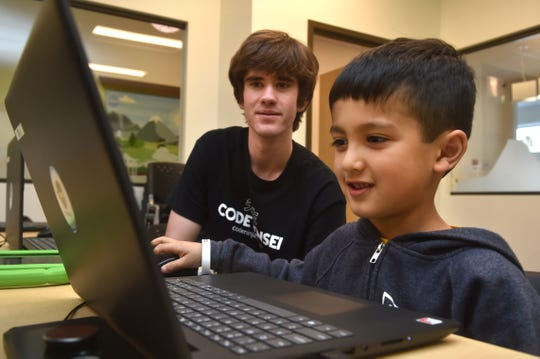 Logan Mobine, right, works on a digital art project with the help of sensei Connor Byrne at the new Code Ninjas dojo in Thousand Oaks. The facility is the first of its kind in Ventura County and the fifth franchise site in California.
