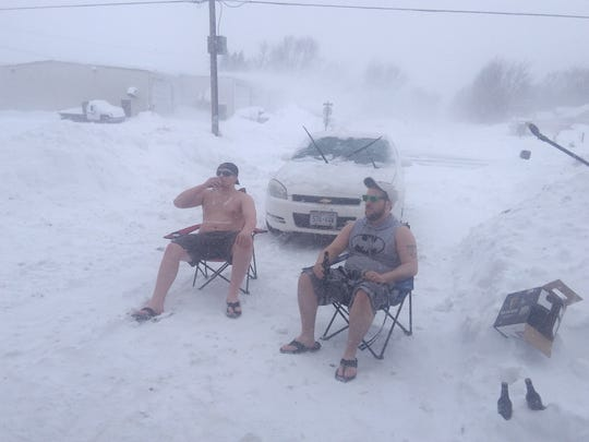 Christopher Devlin and Dameon Strangseld enjoy a drink in the cold Wisconsin snow in Colby.
