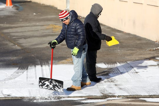 A worker clears the snow as his colleague salts the path outside a car wash business in Sleepy Hollow Feb. 28, 2019 after an overnight light dusting.