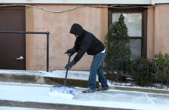Luis Fernandez clears the snow outside a building in Sleepy Hollow Feb. 28, 2019 after an overnight light dusting.