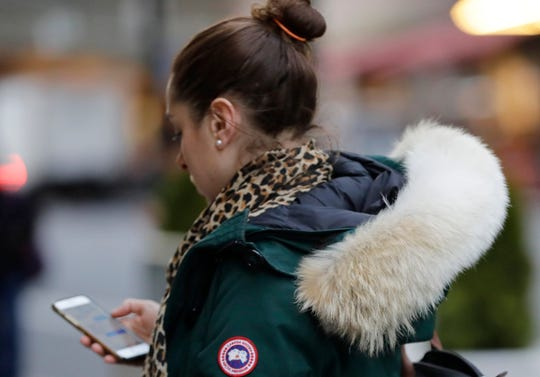 In  this Feb. 14, 2019 photo, a woman in New York wears a Canada Goose coat with the hood trimmed in coyote fur. The fur-trimmed parkas so common on city sidewalks have become a boon to backwoods trappers. The rising demand for coyote fur is largely attributed to its use on Canada Goose parkas. (AP Photo/Frank Franklin II)