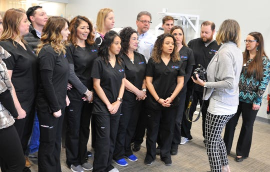 Texas Medical Allergy Chiropractic (TMAC) employees prepare to take a group photograph after participating in a ribbon cutting ceremony celebrating the opening of their business located on Call Field Rd.