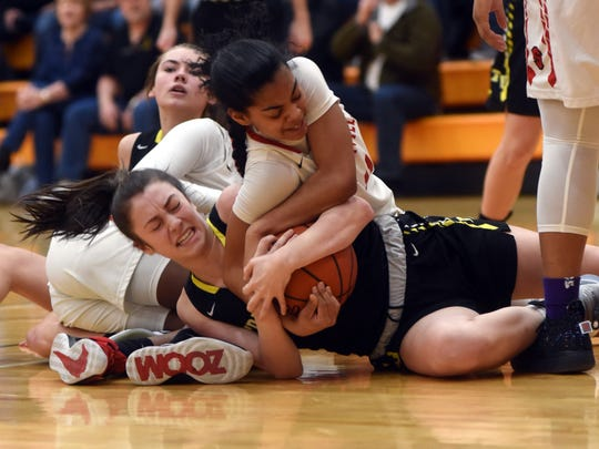 Tri-Valley's Janie McLoughlin, left, gets tied up with Westerville South's Peyton Guice after a scramble for a loose ball in a Division I district semifinal on Wednesday night at Heath High School.