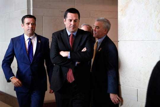 Rep. John Ratcliffe R-Texas, left, and House Intelligence Committee Ranking Member Devin Nunes, R-Calif., center, leave a closed-door meeting of the House Intelligence Committee with testimony from Michael Cohen, President Donald Trump's former personal lawyer, Monday, Feb. 5, 2018, to attend a vote on Capitol Hill in Washington.