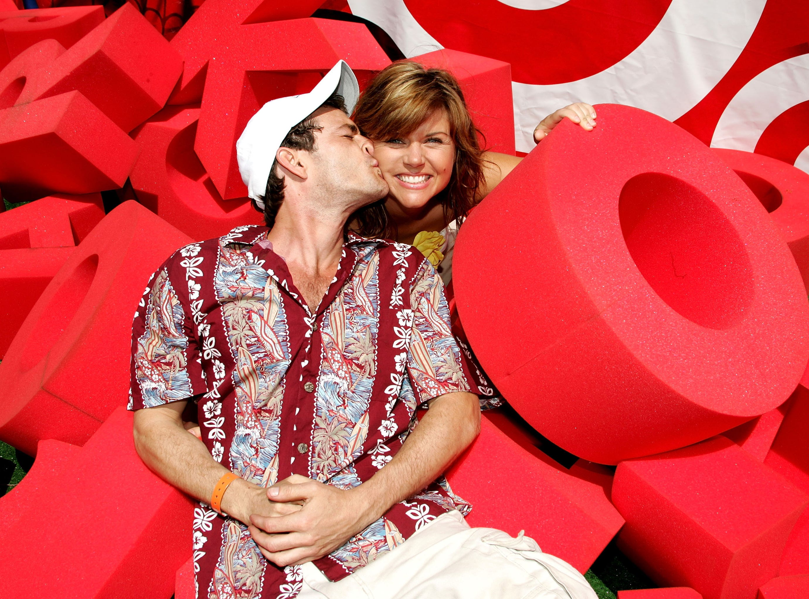 "Actors Luke Perry and Tiffani Thiessen pose at the target crossword puzzle at the ""Target A Time for Heroes to Benefit the Elizabeth Glaser Pediatric AIDS Foundation"" carnival at the Wadsworth Theater grounds June 13, 2004 in Los Angeles, Calif."