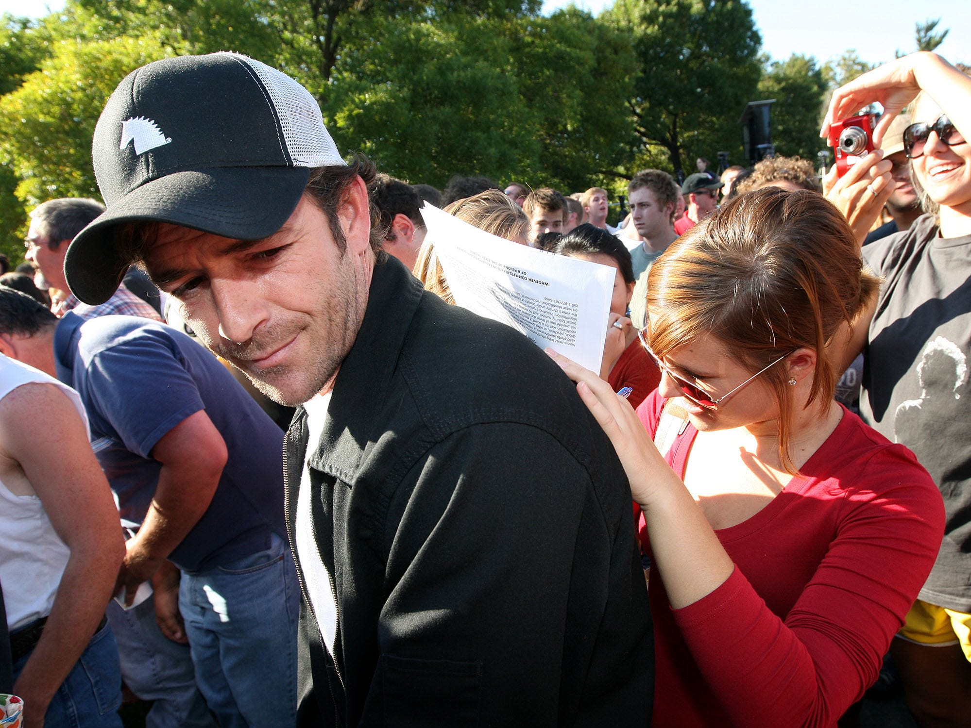 Brooke Short, right, fills out the voter registration form on the back of actor Luke Perry, left, before a Bruce Springsteen concert Sunday, Oct. 5, 2008, on the campus of Ohio State University, in Columbus, Ohio. Perry was encouraging Barack Obama supporters to register and take advantage of Ohio's early voting period.