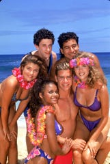 "The cast of ""Saved by the Bell"" pose on the beach. Top row from left: Dustin Diamond, Mario Lopez. Bottom row from left: Tiffani Thiessen, Lark Voorhies, Mark-Paul Gosselaar and Elizabeth Berkley."