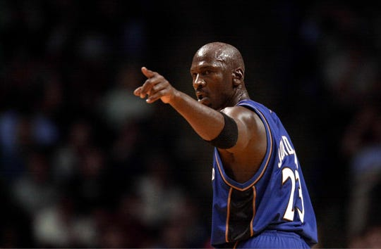 Washington Wizards' Michael Jordan points down court during a game.