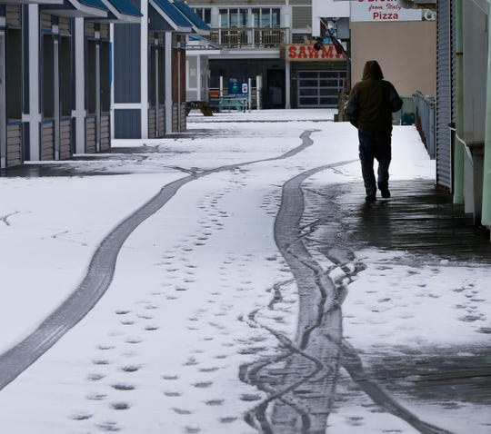 A man walks down the snow covered Seaside Heights boardwalk Friday, March 1, 2019.