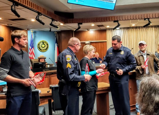 Fire Chief Cande Flores gives an award and special coins for valor to Kelly Russell, among four people honored at the Abilene City Council meeting Thursday. Also honored were, from left, Josh Williams, Scottie Smith and Chance Angley, far right.