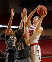 Texas Tech's Brittany Brewer (20) tries to shoot the ball over Iowa State's Bridget Carleton (21) during the first half Tuesday, Feb. 26, 2019, in Lubbock.