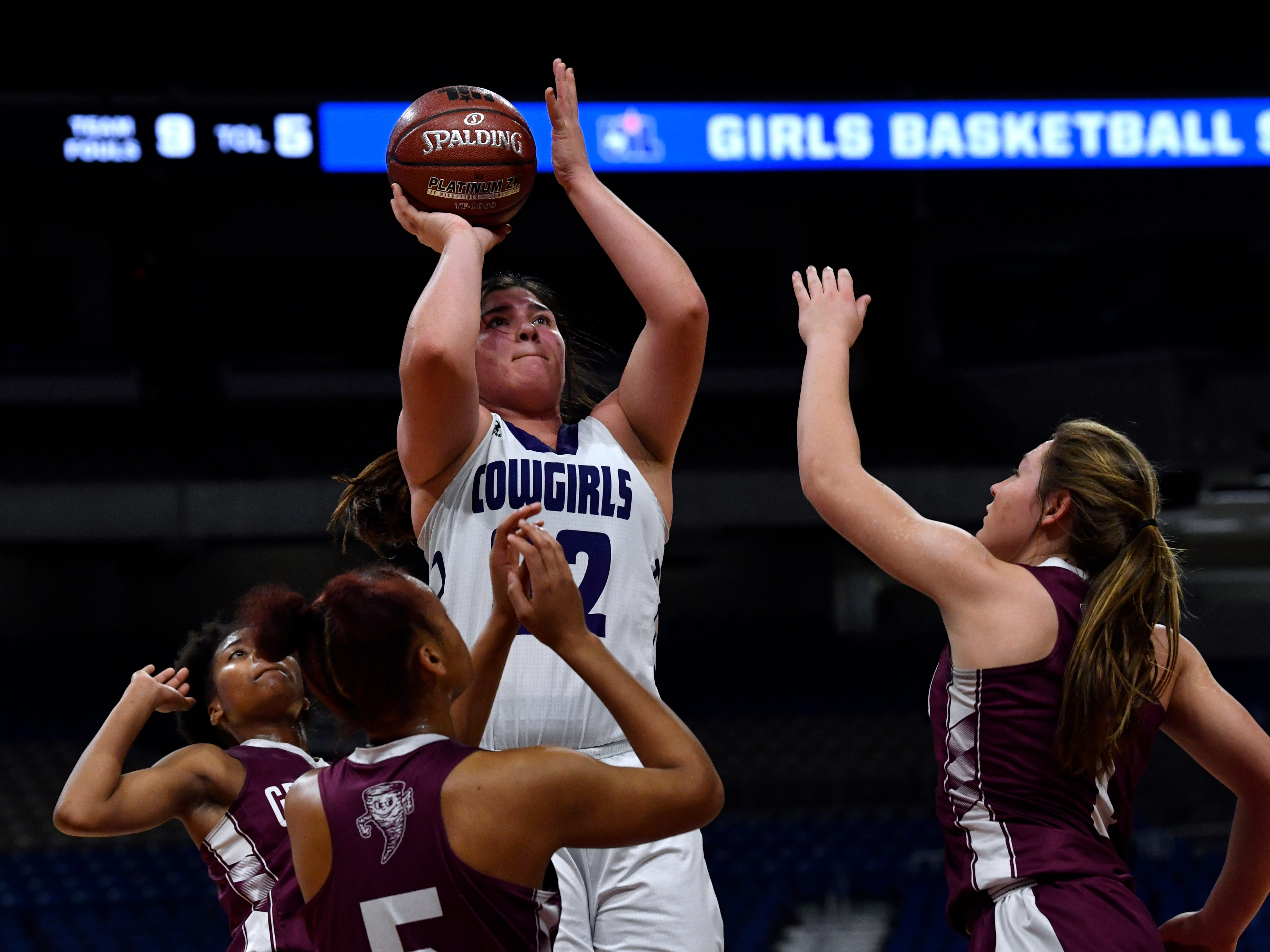 Cowgirls center Ruby Magnus aims for the basket over the heads of Grapeland Sandies players during Friday's UIL Class 2A girls state basketball semifinal at the Alamodome in San Antonio March 1, 2019.