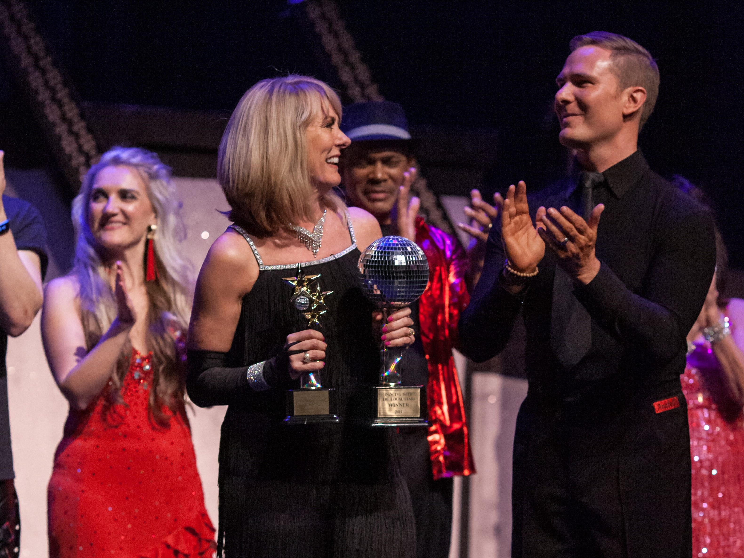 """CarePartners CEO Tracy Buchanan and dance partner Jake Lavender, accept the mirror ball trophy at the inaugural """"Dancing with the Local Stars"""" fundraiser for the American Cancer Society Feb. 24 in Asheville."""