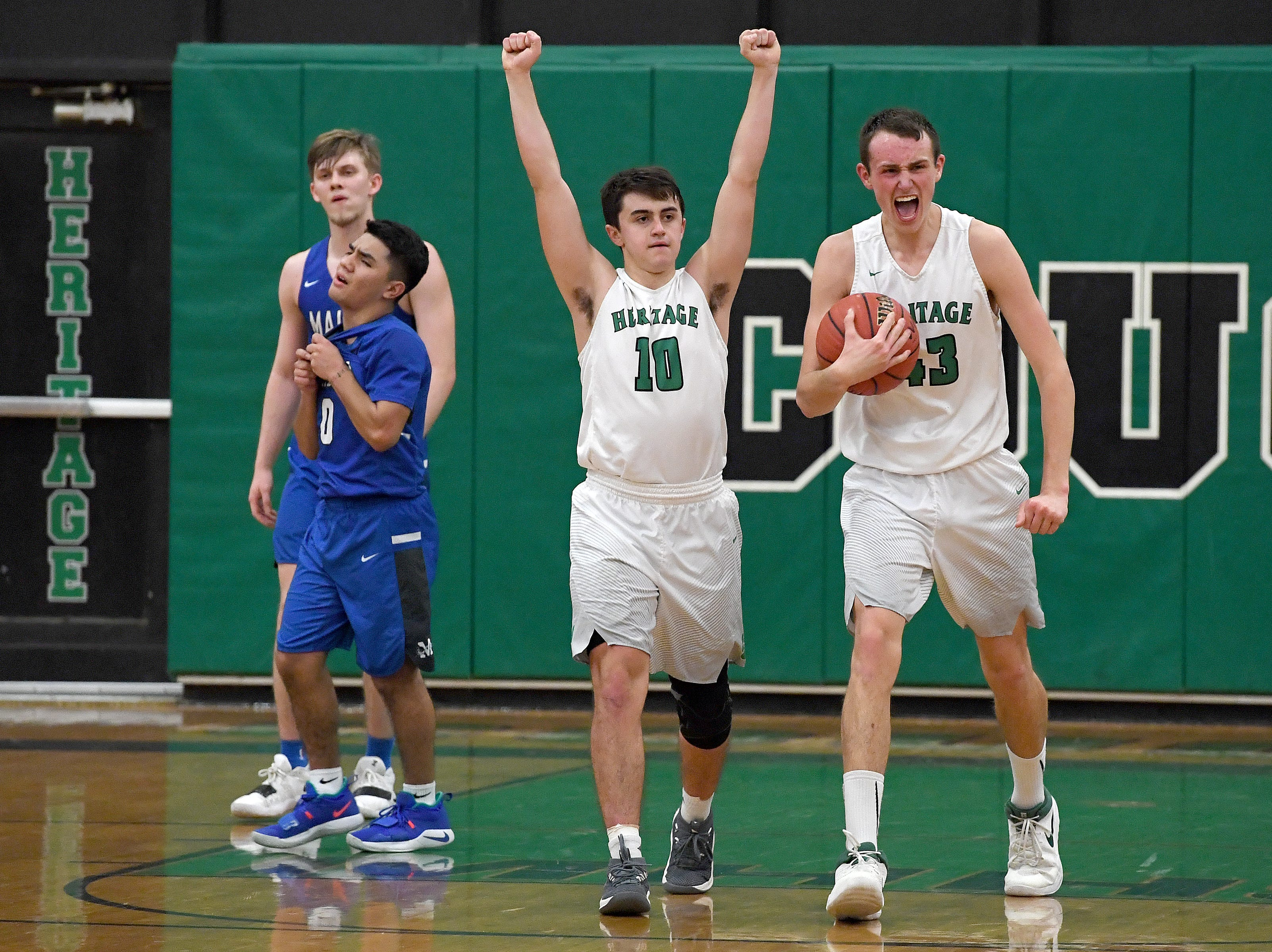 Mountain Heritage's Callin Randolph, left, and Justus Shelton, right, celebrate a call against Maiden during the final seconds of overtime during their playoff game at Mountain Heritage High School on Feb. 28, 2019. The Cougars won 74-69 in overtime to advance to the next round.